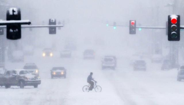 A bicyclist crosses Douglas Avenue in downtown Wichita, Kan., during a heavy snowstorm on Tuesday, Feb. 4, 2014. South-central Kansas is expecting up to seven inches of snow as a winter storm passes through. (AP Photo/The Wichita Eagle, Travis Heying) LOCAL TV OUT; MAGS OUT; LOCAL RADIO OUT; LOCAL INTERNET OUT