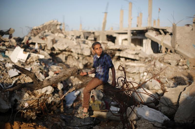 A Palestinian sits amid the rubble of buildings that were destroyed during the 50-day war between Israel and Hamas militants in the summer of 2014, in Gaza City's al-Shejaiya neighbourhood, on March 31, 2015 (AFP Photo/Mohammed Abed)