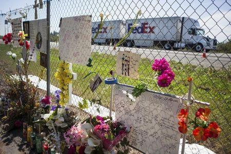 A FedEx truck drives past a makeshift memorial beside Interstate 5 in Orland, California