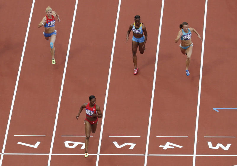 United States' Carmelita Jeter, second from left, crosses the finish line ahead of, from back left, Russia's Olga Belkina, Bahamas' Sheniqua Ferguson and Kazakhstan's Olga Bludova in a women's 100-meter heat during the athletics in the Olympic Stadium at the 2012 Summer Olympics, London, Friday, Aug. 3, 2012. (AP Photo/Mark Duncan)