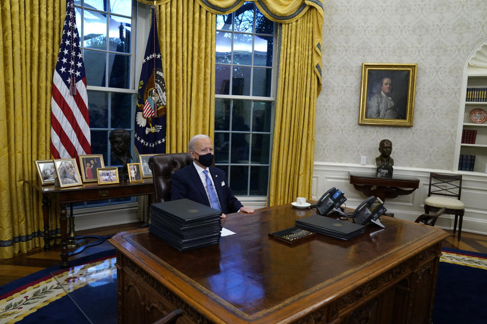 FILE - In this Wednesday, Jan. 20, 2021 file photo, President Joe Biden pauses as he signs his first executive orders in the Oval Office of the White House in Washington. On Friday, Feb. 12, 2021, The Associated Press reported on a manipulated photo circulating online incorrectly asserting it shows President Joe Biden asleep in his seat at the Resolute Desk in the Oval Office with a stack of executive orders in front of him. Biden's head in the post comes from a 2011 event where he appears to briefly doze off as former President Barack Obama delivered a speech on the national debt. (AP Photo/Evan Vucci)