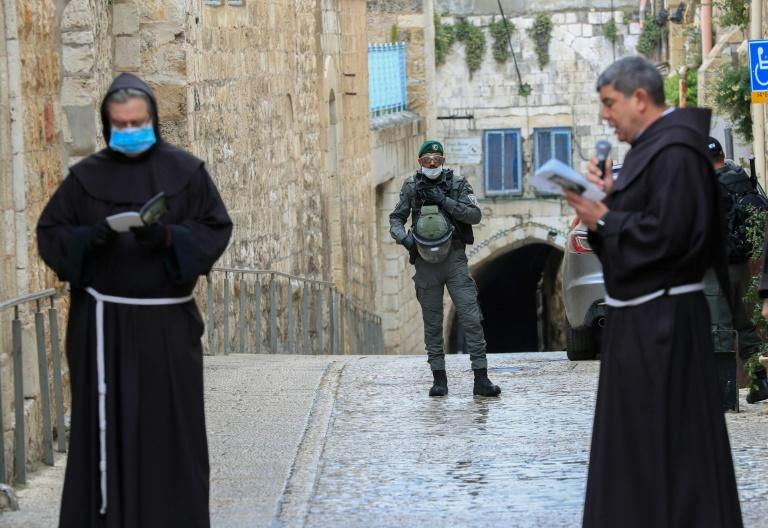 Franciscan friars pray at the First Station of the Cross under the watchful gaze of an Israeli policeman as they retrace Jesus's route through Jerusalem's Old City to his place of crucifixion in a ritual that normally draws thousands of pilgrims