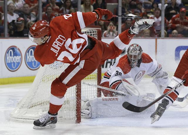 Detroit Red Wings right wing Tomas Jurco, of Slovakia, jumps over Carolina Hurricanes goalie Cam Ward's stick during the second period of an NHL hockey game in Detroit, Friday, April 11, 2014. (AP Photo/Carlos Osorio)