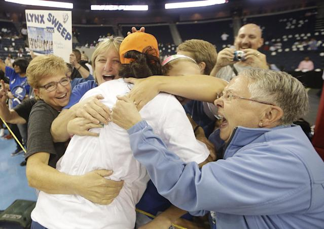 Minnesota Lynx' Monica Wright is embraced by the fans after the second half of Game 3 of the WNBA Finals basketball series against the Atlanta Dream, in Duluth, Ga., Thursday, Oct. 10, 2013. The Minnesota Lynx won 86- 77. (AP Photo/John Bazemore)