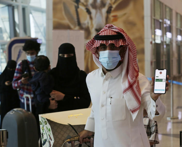 Saudi passenger, Sultan Saeed Al-Shahrani, shows his vaccination certificate on his phone, at a checkpoint in King Abdulaziz International Airport in Jiddah, Saudi Arabia, Monday, May 17, 2021. Vaccinated Saudis will be allowed to leave the kingdom for the first time in more than a year as the country eases a ban on international travel that had been in place to try and contain the spread of the coronavirus and its new variants. (AP Photo/Amr Nabil)