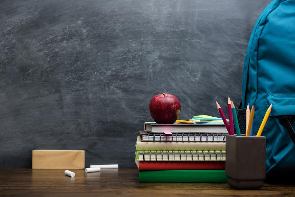 Stack of books, colorful stationery and education supplies on wooden table in classroom with blackboard in background