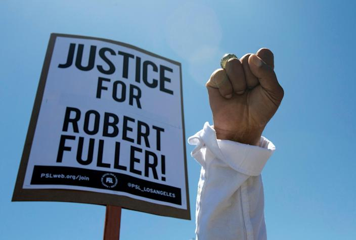 A demonstrator raises his fist during a protest rally for Robert Fuller whose body was found hanging from a tree a block from Palmdale City Hall, in the aftermath of the death in Minneapolis police custody of George Floyd, in Palmdale, California, U.S., June 13, 2020. (Ringo Chiu/Reuters)