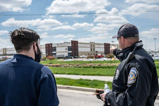 PHOTO: A FedEx employee speaks with a police officer about details relating to his place of work, a FedEx Ground facility, on April 16, 2021, in Indianapolis. (Jon Cherry/Getty Images)