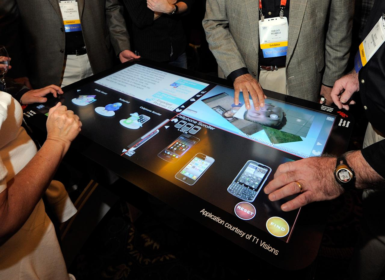 LAS VEGAS, NV - JANUARY 08:  Attendees try a prototype 3M Touch Systems 46-inch, projected capacitive display during a press event at The Venetian for the 2012 International Consumer Electronics Show (CES) January 8, 2012 in Las Vegas, Nevada. The display utilizing technology from T1 Visions features a six-millisecond response to touch time, handles up to 20 finger touches at once and rejects accidental palm touches. CES, the world's largest annual consumer technology trade show, runs from January 10-13 and is expected to feature 2,700 exhibitors showing off their latest products and services to about 140,000 attendees.  (Photo by Ethan Miller/Getty Images)