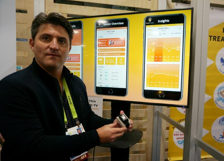 Jerry Wilmink of CarePredict holds a wearable tech band that can help monitor seniors in assisted living and help predict falls or other health issues at the 2019 Consumer Electronics Show