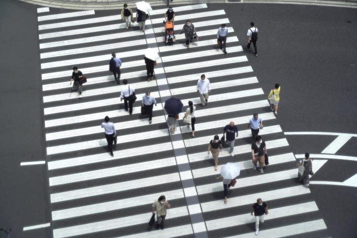 People walk across a crossing near Tokyo Station in Tokyo Thursday, July 29, 2021, a day after the record-high coronavirus cases were found in the Olympics host city. (AP Photo/Kantaro Komiya)