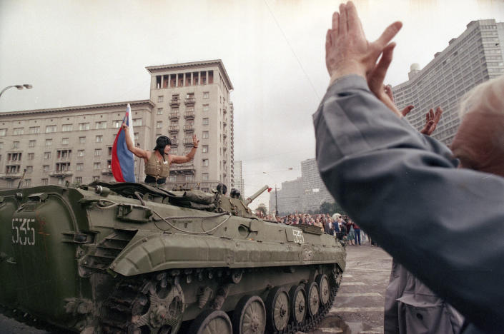 FILE - In this Wednesday, Aug. 21, 1991 file photo, a crowd greet a jubilant tank officer with the Russian national flag in the street of Moscow amid reports that the coup has failed, in Russia. When a group of top Communist officials ousted Soviet leader Mikhail Gorbachev 30 years ago and flooded Moscow with tanks, the world held its breath, fearing a rollback on liberal reforms and a return to the Cold War confrontation. But the August 1991 coup collapsed in just three days, precipitating the breakup of the Soviet Union that plotters said they were trying to prevent. (AP Photo/Czarek Sokolowski, File)