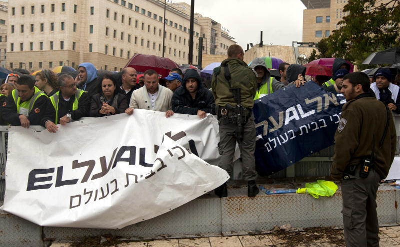 Israeli border police officers stand guard as Israeli airline workers hold signs during a demonstration in front of the prime minister's office in Jerusalem, Sunday, April 21, 2013. Israel's Cabinet on Sunday approved a deal to allow more EU flights, hours after the country's airlines went on strike out of concerns that the agreement would cost them jobs and possibly even ruin their companies.(AP Photo/Sebastian Scheiner)