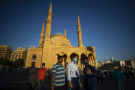 Muslim worshippers wearing masks to help stop the spread of the coronavirus, take a selfie after offered Eid al-Adha prayer outside the Mohammad al-Amin Mosque, in Beirut, Lebanon, Friday, July 31, 2020. (AP Photo/Hassan Ammar)