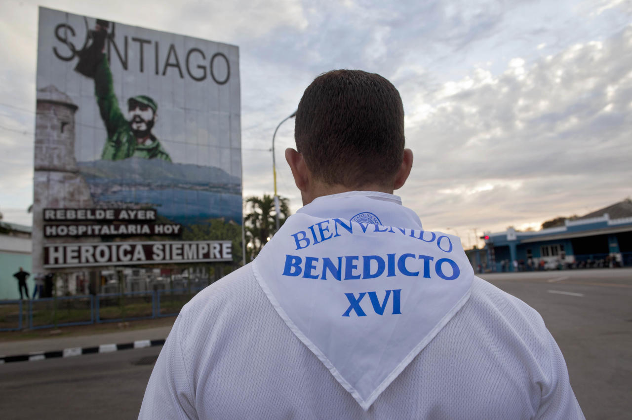 "A man wears a neckerchief that reads in Spanish ""Welcome Pope Benedict XVI"" in front of a billboard with an image of Cuba's leader Fidel Castro that reads in Spanish ""Santiago, yesterday rebel, today hospitable, always heroic"" in Santiago de Cuba, Cuba, Sunday, March, 25, 2012. Pope Benedict XVI will arrive to Cuba on Monday. (AP Photo/Esteban Felix)"