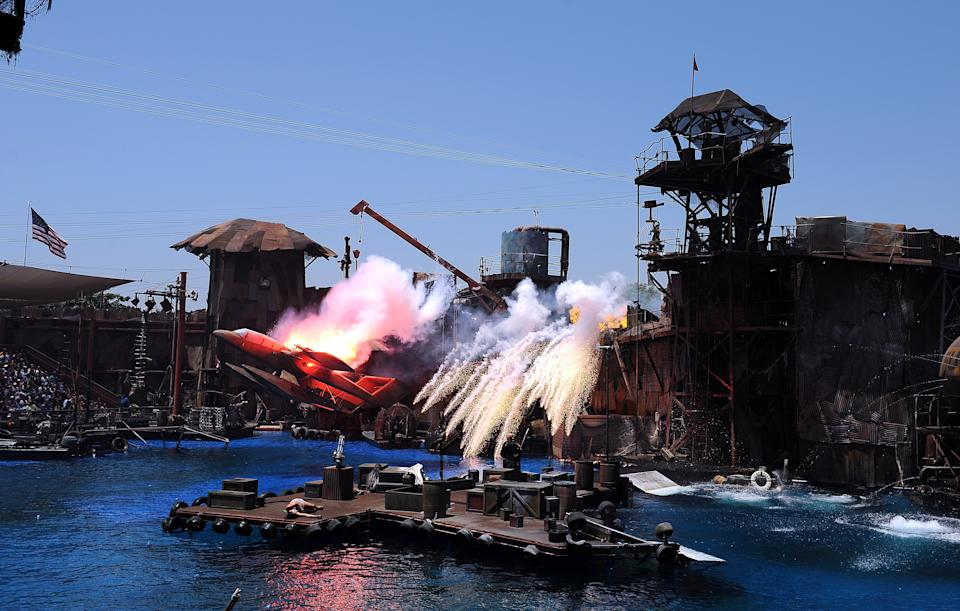 """People enjoy Waterworld's attraction at Universal Studios in Hollywood, July 20, 2010. Universal Studios Hollywood is the original Universal Studios theme park, created initially to offer tours of the real Universal Studios soundstages and sets. This grew over the years into a full-blown theme park - the narrated tram (formerly """"Glamortram"""") tour still runs through the studio's active backlot, but the staged events, stunt demonstrations and high-tech rides overshadow the motion-picture production that once lured fans in Universal Studios Hollywood. AFP PHOTO GABRIEL BOUYS (Photo credit should read GABRIEL BOUYS/AFP via Getty Images)"""