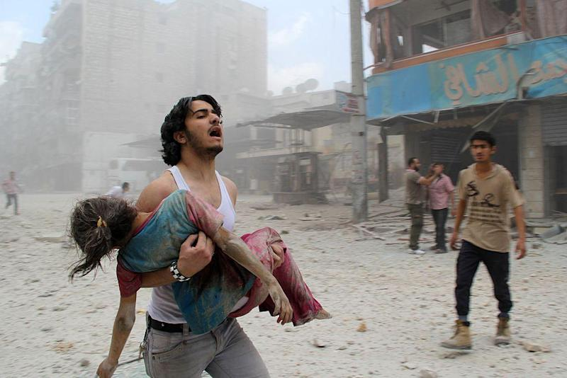 A man carries a young girl injured in a regime barrel bomb attack in the Syrian city of Aleppo on June 3, 2014. Almost 500,000 people have lost their lives in six years of conflict: AFP/Getty