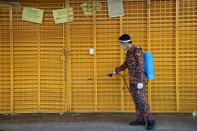 A firefighter disinfects a closed shop during the movement control order due to the outbreak of the coronavirus disease (COVID-19), in Kuala Lumpur
