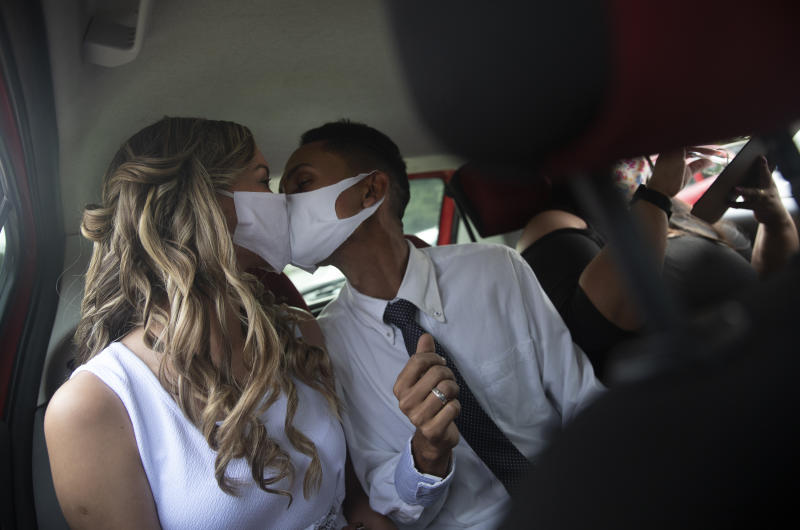 Wearing masks to prevent the spread of the new coronavirus, Thiago do Nascimento, right, and Keilla de Almeida kiss during their drive-thru wedding at the registry office in the neighborhood of Santa Cruz, Rio de Janeiro, Brazil, Thursday, May 28, 2020. Couples have begun turning to this unconventional union at a notary in Santa Cruz since the COVID-19 started battering Brazil. (AP Photo/Silvia Izquierdo)