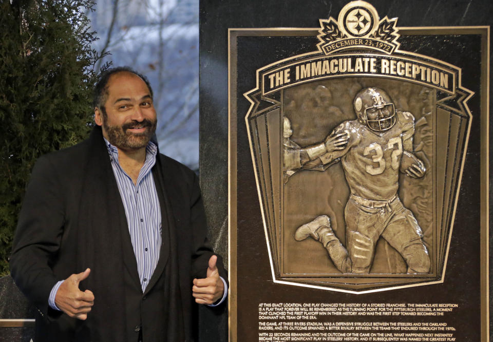 """FILE - In this Dec. 22, 2012, file photo, former Pittsburgh Steelers Hall of Fame running back Franco Harris stands on the spot of the """"Immaculate Reception"""" after a marker commemorating the 40th anniversary of the play was unveiled where Three Rivers Stadium once stood on the North Side of Pittsburgh. Harris' scoop of a deflected pass and subsequent run for the winning touchdown in a 1972 playoff victory against Oakland _ has been voted the greatest play in NFL history. A nationwide panel of 68 media members chose the Immaculate Reception as the top play with 3,270 points and 39 first-place votes. (AP Photo/Gene J. Puskar, File)"""