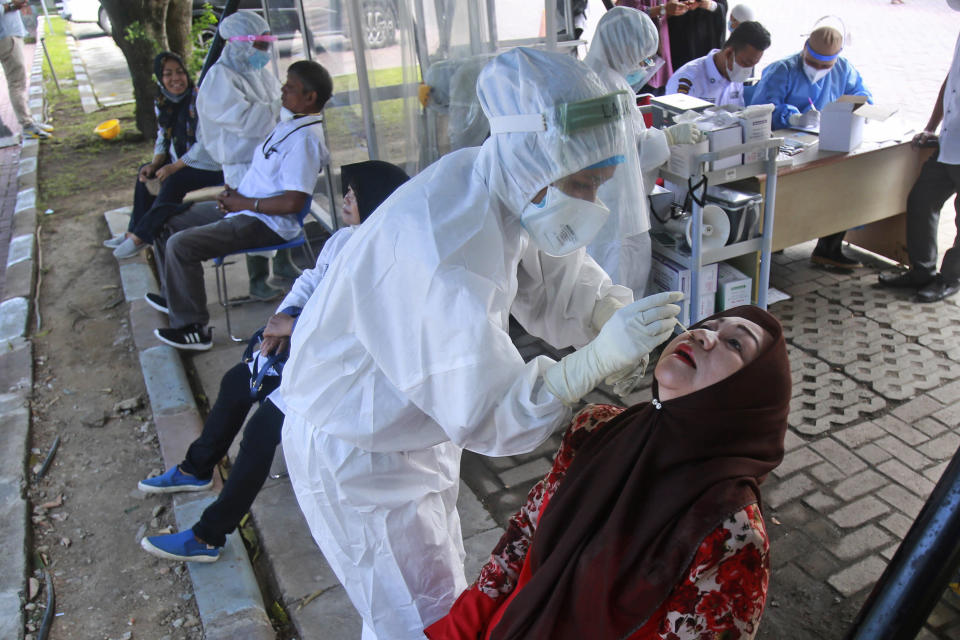 A medical workers collect nasal swab samples from a woman to be tested for coronavirus during a COVID-19 screening at University of North Sumatra in Medan, Indonesia, Monday, June 21, 2021. Indonesia has reported more coronavirus cases than any other country in Southeast Asia. (AP Photo/Binsar Bakkara)