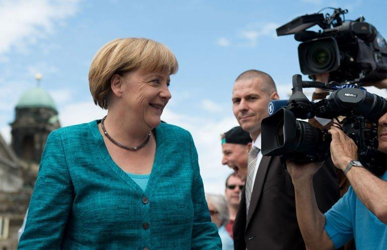 A cameraman films German chancellor Angela Merkel as she arrives for a meeting on June 23, 2013 in Berlin
