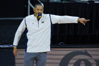 Michigan head coach Juwan Howard directs his team as they played Maryland in the first half of an NCAA college basketball game at the Big Ten Conference tournament in Indianapolis, Friday, March 12, 2021. (AP Photo/Michael Conroy)