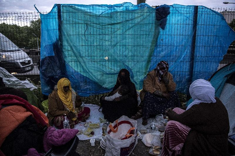Somalis having an evening meal at their camp at the Porte d'Aubervilliers. Local residents have complained about the acrid smoke of migrants' cooking fires. (AFP Photo/Christophe ARCHAMBAULT)