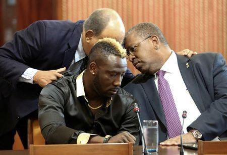 West Indies all-rounder Andre Russell (C front) sits at a desk during a meeting of an independent anti-doping tribunal at the Jamaica Conference Centre next to his lawyers Patrick Foster (L, rear, partially obscured) and Donovan Walker, in Kingston, Jamaica January 31, 2017. REUTERS/Gilbert Bellamy