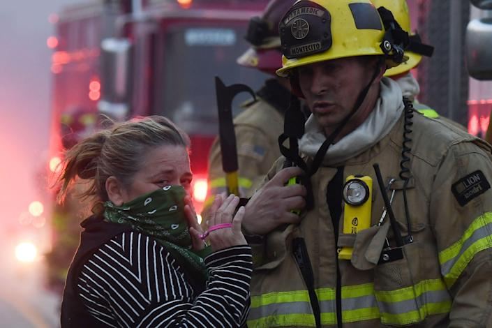 <p>A local resident speaks with firefighters stationed along Pacific Coast Highway (Highway 1) to battle the Woolsey Fire on Nov. 9, 2018 in Malibu, Calif. (Photo: Robyn Beck/AFP/Getty Images) </p>