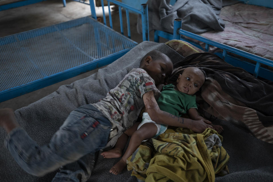 Tigrayan 5-year-old refugee Micheale Gebremariam hugs his 4-month-old sister, Aden, after waking up early in the morning in their shelter in Hamdayet, eastern Sudan, near the border with Ethiopia, on March 21, 2021. (AP Photo/Nariman El-Mofty)