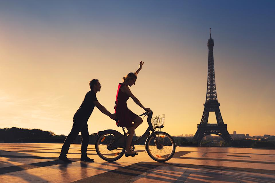 happy couple having fun in Paris riding bicycle near Eiffel tower, silhouettes