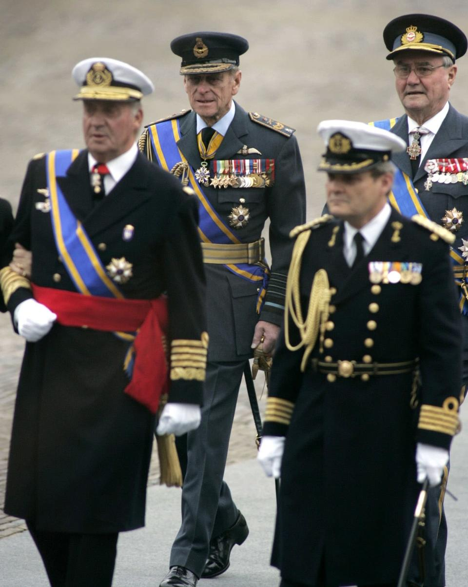 FILE - In this Saturday Dec. 11, 2004, file photo, King Juan Carlos of Spain, foreground left, Prince Philip, husband of Britain's Queen Elizabeth II, center rear, and Prince Henrik of Denmark, rear right, arrive for the funeral of Prince Bernhard of the Netherlands at Nieuwe Kerk, or New Church, in the center of Delft, The Netherlands. Prince Philip's life spanned just under an entire century of European history. His genealogy was just as broad, with Britain's longest-serving consort linked by blood and marriage to most of the continent's royal houses. (AP Photo/Fred Ernst, File)
