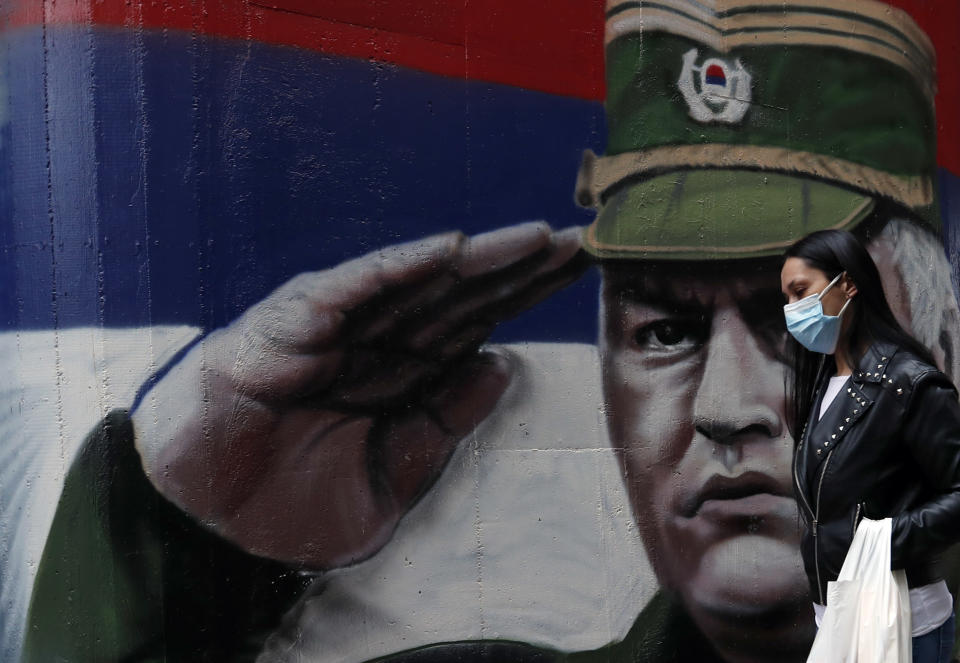 FILE — In this Thursday, Nov. 12, 2020 file photo, a woman wearing a mask against the spread of the coronavirus walks past a mural depicting former Bosnian Serb wartime general Ratko Mladic in Belgrade, Serbia. U.N. judges on Tuesday, June 8, 2021 deliver their final ruling on the conviction of former Bosnian Serb army chief Radko Mladic on charges of genocide, war crimes and crimes against humanity during Bosnia's 1992-95 ethnic carnage. Nearly three decades after the end of Europe's worst conflict since World War II that killed more than 100,000 people, a U.N. court is set to close the case of the Bosnian War's most notorious figure. (AP Photo/Darko Vojinovic, File)