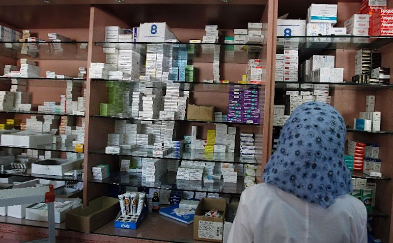 A pharmacist looks for medication at a Damascus pharmacy on September 17, 2013 in Syria, where drug production has come to a near total halt