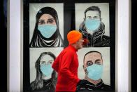 A runner passes by a window displaying portraits of people wearing face coverings to help prevent the spread of the coronavirus, Monday, Nov. 16, 2020, in Lewiston, Maine. An executive order by Gov. Janet Mills' requires Maine citizens to wear face coverings in public settings, regardless of the ability to maintain physical distance. (AP Photo/Robert F. Bukaty)