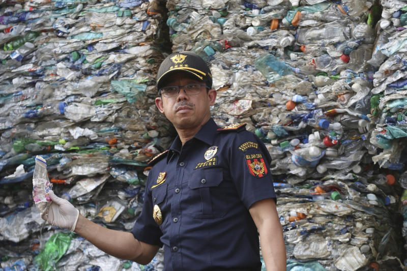 Director General of Indonesian Customs and Excise Heru Pambudi holds plastic bottle from containers full of plastic waste at Tanjung Priok port in Jakarta, Indonesia Wednesday, Sept. 18, 2019. Indonesia is sending hundreds of containers of waste back to Western nations after finding they were contaminated with used plastic and hazardous materials. (AP Photo/Achmad Ibrahim)