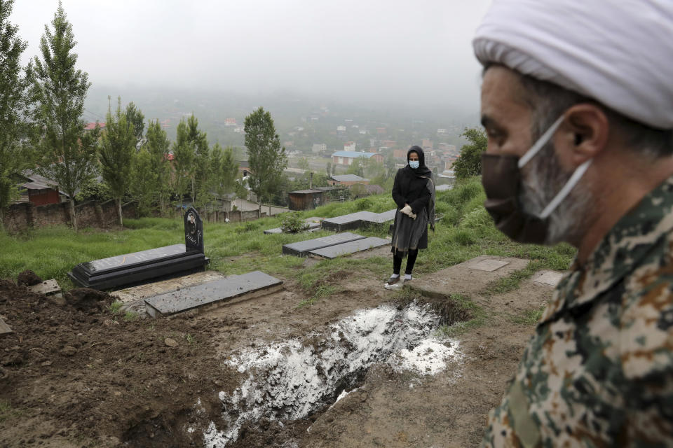 FILE - In this April 30, 2020, file photo, a woman wearing mask and gloves, prays at the grave of her mother who died from the coronavirus, at a cemetery in the outskirts of the city of Babol, in northern Iran. As coronavirus infections reached new heights in Iran, overwhelming its hospitals and driving up its death toll, the country's health minister gave a rare speech criticizing his own government's refusal to enforce basic health measures. (AP Photo/Ebrahim Noroozi, File)