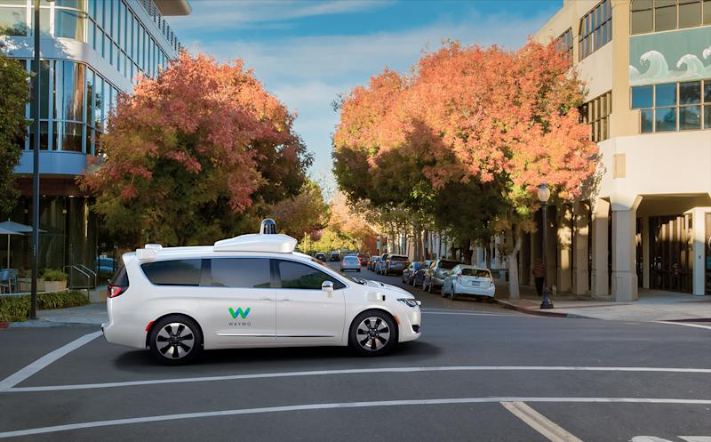 Waymo self-driving minivan crossing an intersection with fall trees in the background.