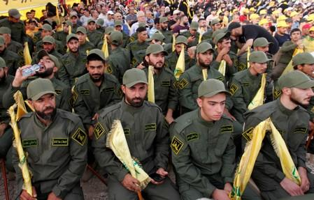 Lebanon's Hezbollah members hold party flags as they listen to their leader Sayyed Hassan Nasrallah addressing his supporters via a screen during a rally marking the anniversary of the defeat of militants near the Lebanese-Syrian border, in al-Ain