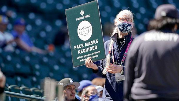 PHOTO: An usher holds up a sign reminding fans to wear face masks during a baseball game between the Seattle Mariners and the Los Angeles Dodgers, April 20, 2021, in Seattle. (Ted S. Warren/AP)