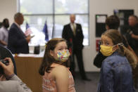 Two Camden Elementary School students in masks listen as South Carolina Gov. Henry McMaster talks about steps the school is taking to fight COVID-19, Wednesday, Sept. 15, 2021, in Camden, S.C. McMaster has adamantly and repeatedly come out against requiring masks in schools even as the average number of daily COVID-19 cases in the state has risen since early June. (AP Photo/Jeffrey Collins)