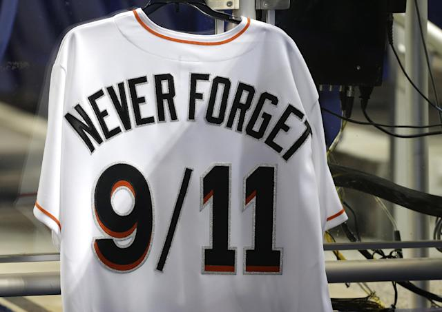 A jersey hangs in the Miami Marlins dugout commemorating the 12th anniversary of the 9/11 attacks before a baseball game against the Atlanta Braves, Wednesday, Sept. 11, 2013, in Miami. (AP Photo/Lynne Sladky)