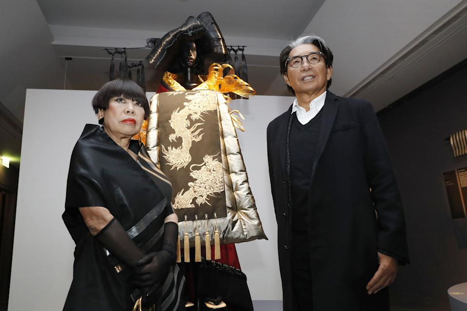 """Japanese fashion designer Junko Koshino (L) and Japanese-French fashion designer Kenzo Takada (R) pose next to a Kimono created by Koshino during the inauguration of the exhibition """"Kimono - Au bonheur des dames"""" at the Guimet museum in Paris, on February 21, 2017. The exhibition will run from February 22 to May 22, 2017. / AFP / PATRICK KOVARIK / RESTRICTED TO EDITORIAL USE - MANDATORY MENTION OF THE ARTIST UPON PUBLICATION - TO ILLUSTRATE THE EVENT AS SPECIFIED IN THE CAPTION (Photo credit should read PATRICK KOVARIK/AFP via Getty Images)"""
