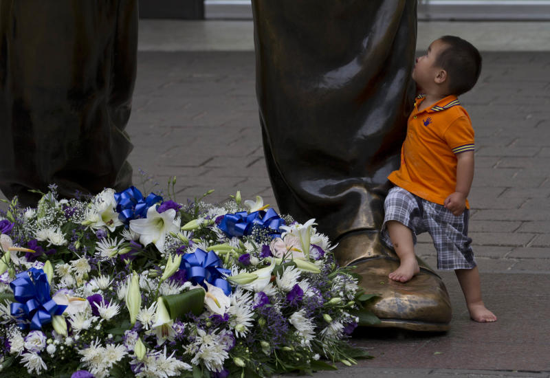 A child looks up at a giant bronze statue of former president Nelson Mandela, on Mandela Square in Sandton, Johannesburg, Friday, Dec 6.2013. Flower tributes were placed on the square after Mandela died Thursday at his Johannesburg home after a long illness. He was 95. (AP Photo/Athol Moralee)
