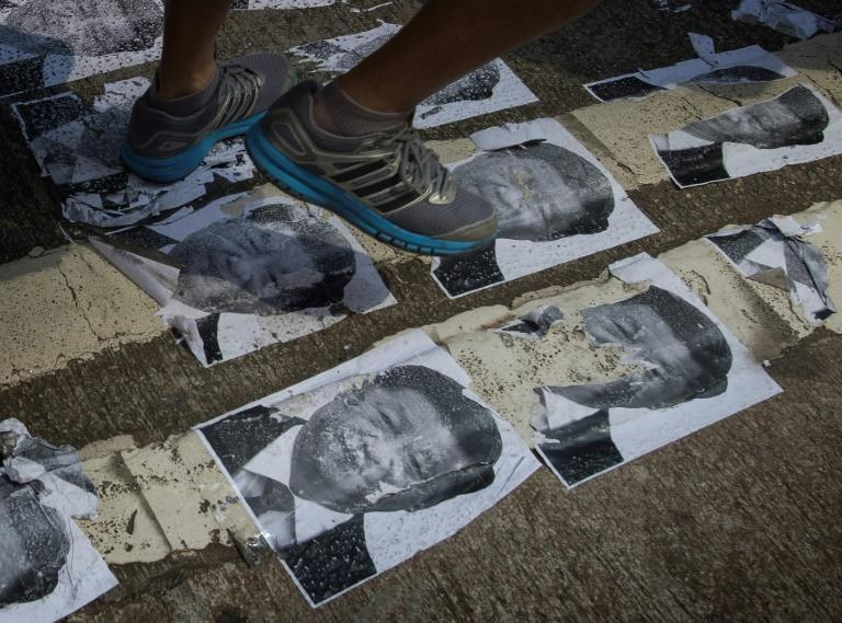 While a huge celebration was held in Beijing, pictures of Chinese leader Xi Jinping were trampled on in Hong Kong (AFP Photo/Mark RALSTON)