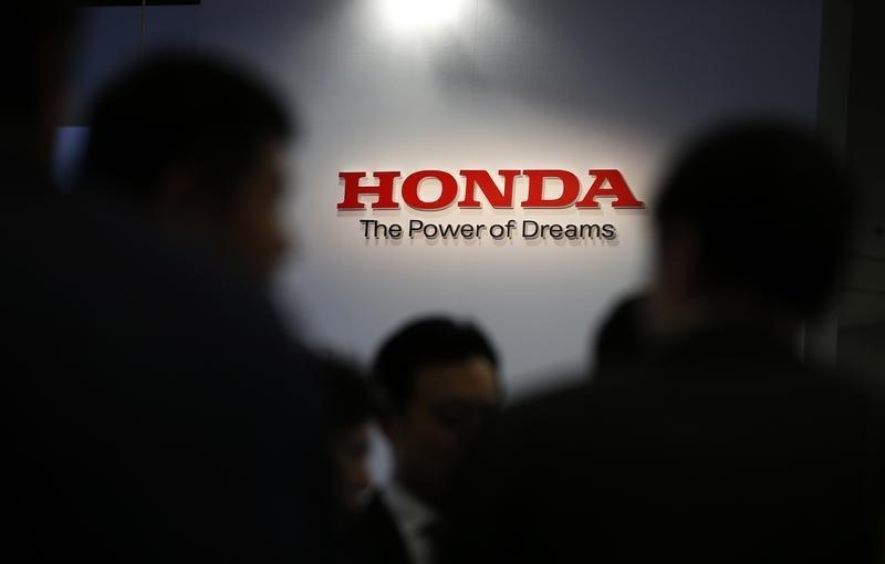 """A logo of Honda Motor Co is seen behind journalists after the unveiling event for the company's all-new hybrid sedan """"Grace"""" in Tokyo"""