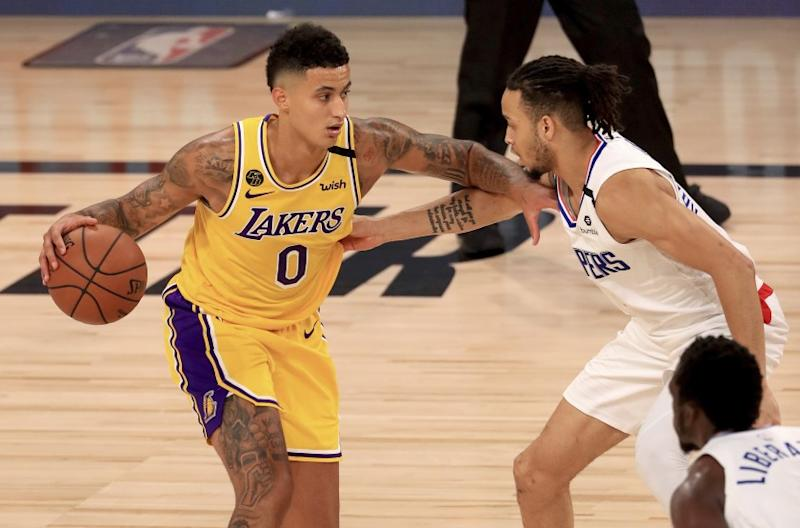 Los Angeles Lakers' Kyle Kuzma (0) is defended by Los Angeles Clippers' Amir Coffey (7) during the third quarter of an NBA basketball game Thursday, July 30, 2020, in Lake Buena Vista, Fla. (Mike Ehrmann/Pool Photo via AP)