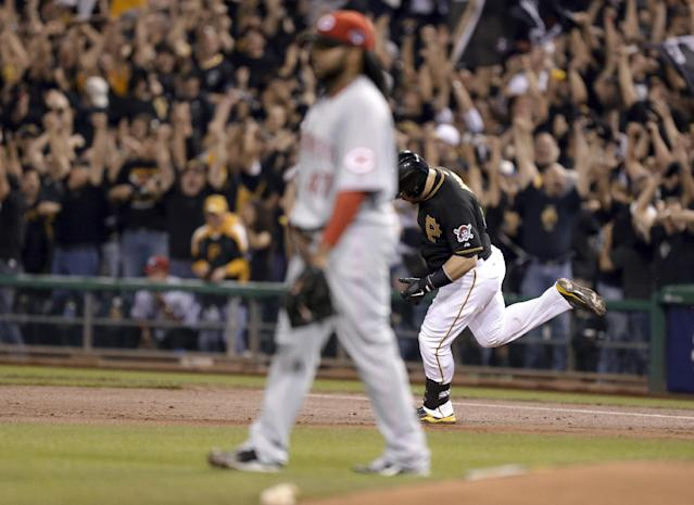 Russell Martin, right, runs past first behind Cincinnati Reds starting pitcher Johnny Cueto after hitting a home run in the second inning of the NL wild-card playoff baseball game Tuesday, Oct. 1, 2013, in Pittsburgh. (AP Photo/Gene J. Puskar)