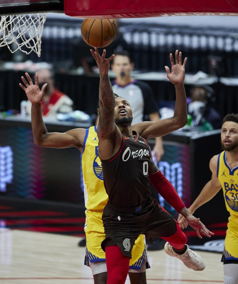 Portland Trail Blazers guard Damian Lillard scores against the Golden State Warriors during the second half of an NBA basketball game in Portland, Ore., Wednesday, March 3, 2021. (AP Photo/Craig Mitchelldyer)